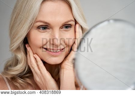Happy 50s Middle Aged Woman Model Touching Face Skin Looking In Mirror. Smiling Mature Older Lady Pa