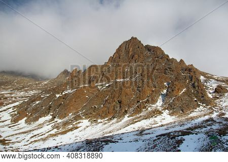 A Rocky Red Mountain With A Snow-capped Foot Against The Backdrop Of Thick Clouds In Sunlight In Tuy