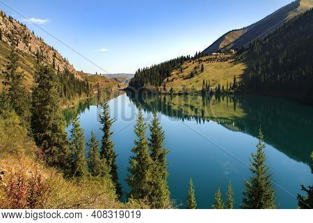 Alpine Kolsai Lake In Mountain Gorge Surrounded By Trees On A Sunny Summer Day, Kazakhstan. Sunny Su