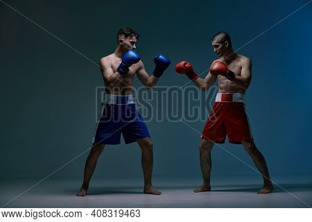 Sparring Of Two Fighting Males Boxers During Battle In Blue Studio Light, Martial Arts, Mixed Fight