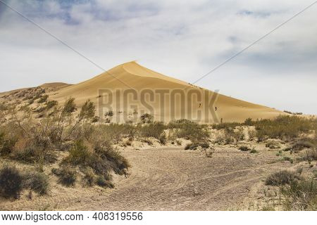 Huge Sand Dune With Bushes At The Foot And Road In Summer, Against The Blue Sky With Clouds, Singing