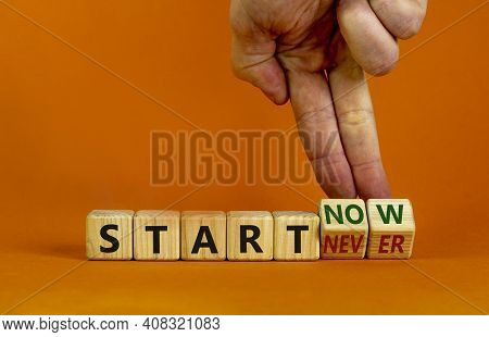 Start Now Or Never Symbol. Businessman Turns Wooden Cubes And Changes Words 'start Never' To 'start