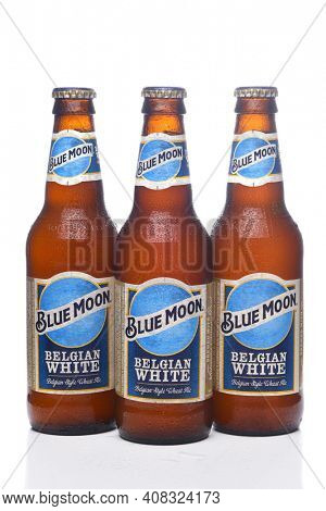 IRVINE, CALIFORNIA - 12 JUNE 2020: Three cold bottles of Blue Moon Belgian White Wheat Ale with condensation isolated on white with reflection.
