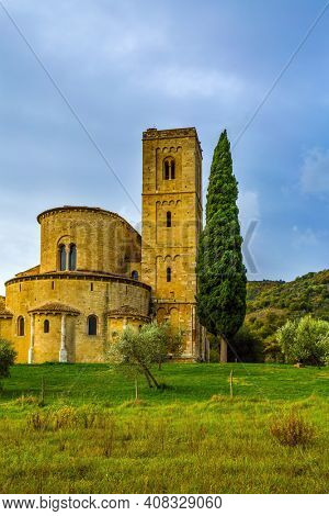 Picturesque Tuscany. Ancient medieval magnificent abbey of San Antimo. Autumn day. Tall slender cypress adorns the facade of the abbey.  The concept of active, rural and photo tourism