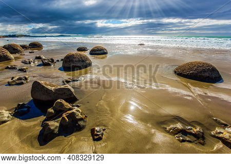 Low tide in the Pacific ocean. The South Island of New Zealand. Moeraki Boulders is the group of large spherical boulders. Popular tourist attraction. The concept of exotic and ecological tourism