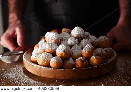 Man Sprinkles Powdered Sugar Onbaked Castagnole. Round Biscuits With Sugar For The Carnival Of Venic