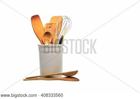 Wooden Utensils For Cooking Are In A White Glass. Kitchen Spoons, Scoops, Forks Isolated On White Ba