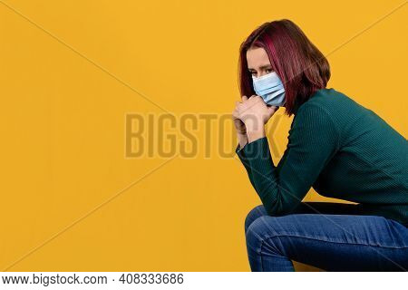 Mental Health And Coping During Covid-19. Disturbed Worried Young Woman In Face Surgical Mask On Yel