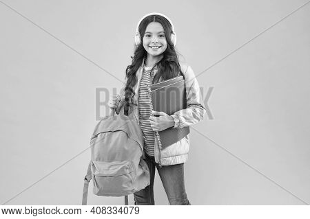 Educating Ear To Music. Happy Kid Wear Earphones. Music Education. Little Girl Hold Books And Bag. M