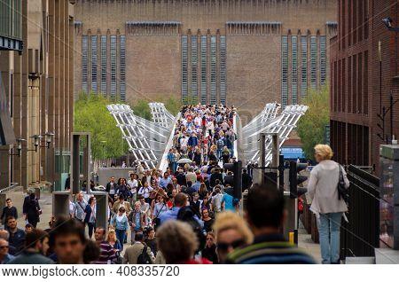 LONDON, UK - CIRCA JUNE 2011: People on the Millennium Bridge. The Millennium Bridge is a steel suspension bridge over the Thames River for pedestrians.