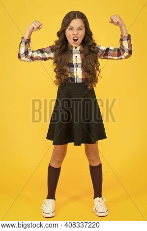 Feeling Power Of Being A Girl. Strong Girl Yellow Background. Little Girl Show Strength Flexing Arms
