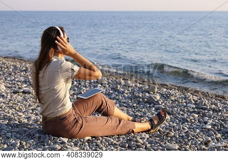 Young Woman Sits On Deserted Pebble Shore And Listens To Music In Headphones, Looking At The Sea In