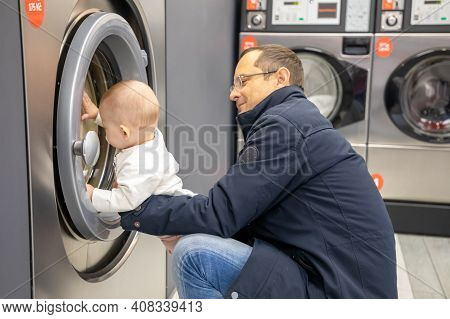Prague, Czech Republic - 16.12.2020: Man With His Baby Waiting For Laundry In Laundry Room With Spee