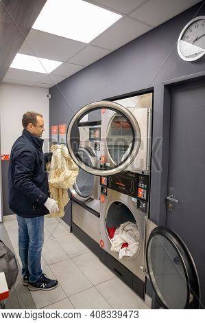 Prague, Czech Republic - 16.12.2020: Man Loading Washing Machine For Laundry In Laundry Room With Sp