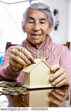Closeup Of A Hand Of A Senior Woman Sitting At Her Home Saving Money