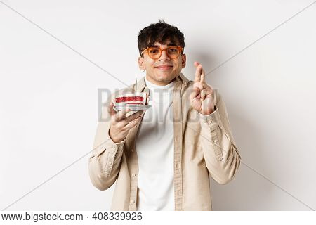 Wishful Handsome Guy In Glasses Making Wish On Birthday Cake, Standing With Fingers Crossed And Happ