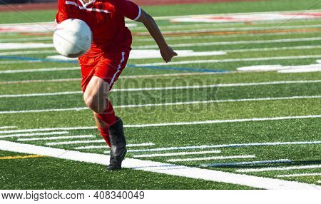 Selective Focus On A High School Soccer Player In A Red Uniform Chasing A High Bauncing Ball During