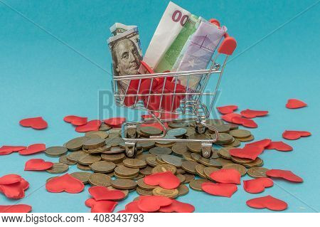 The Mini Cart From The Supermarket Stands On Money And Little Hearts. Close-up, Blue Background. The
