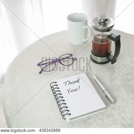 Thank You, Words Written On Notepad, Next To French Press With Brew Coffee, Cup And Eyewear On Top O