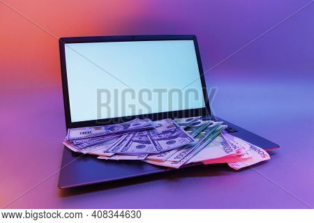 Mock Up Laptop With White Screen And Bundles Of Dollars And Euros Against A Background Of Colorful B