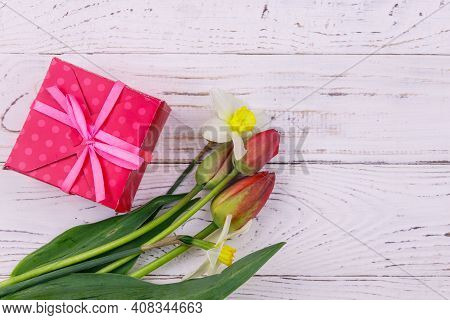 Gift Box And Bouquet Of Red Tulips And Daffodils On White Wooden Background. Concept Of Valentine's