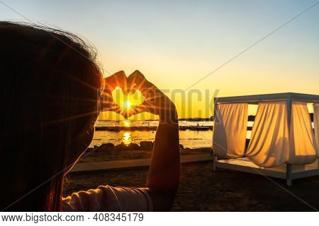 Woman Showing With Her Hands Heart, Love Symbol Witch Trough Shines Sunstar With Sunrays, At Beautif