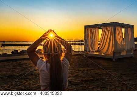 Young Girl Holding Sun In Her Hands Witch Trough Shines Sunstar With Sunrays, At Beautiful Sunset On