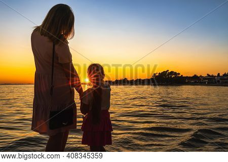 Mother And Daughter Holding Hands, Admiring Beautiful Sunset At Adriatic Sea Beach. Silhouette Of A