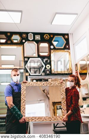 Small business owners with face masks during coronavirus Covid-19, holding a handmade mirror in a local store.
