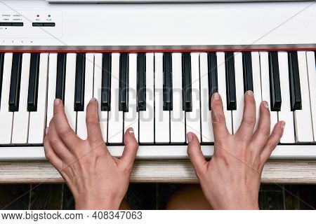 Woman's Hands Playing Electronic Digital Piano At Home. The Woman Is Professional Pianist Arranging