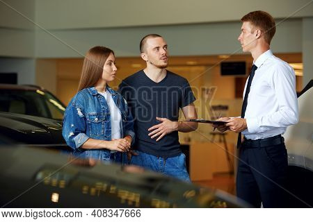 A Friendly Car Dealer Shows And Explains To A Young Married Couple All The Pros And Cons Of A Brand