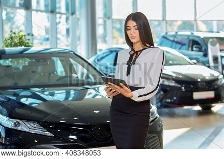 Portrait of a pretty girl sales Manager of Asian appearance in a car dealership with a tablet in her