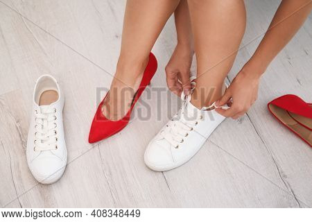 Woman Taking Off Uncomfortable Shoes And Putting On Sneakers In Office, Closeup. Tired Feet After We