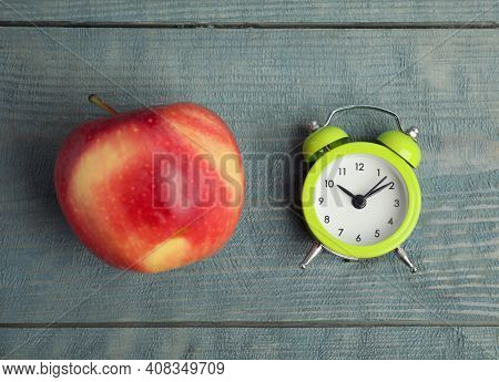 Alarm Clock And Apple On Light Blue Wooden Table, Flat Lay. Meal Timing Concept