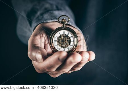 Man holding pocket watch concept for time, deadline and urgency
