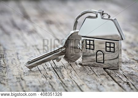 House key on a house shaped keychain on wood background concept for real estate, moving home or renting property