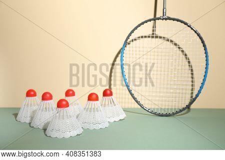 Shuttlecocks And Racquet Against Beige Background. Badminton Equipment