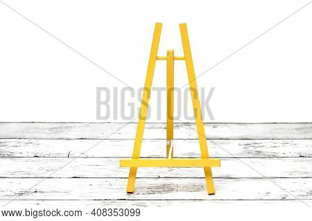 Wooden Small Easel On A White Grunge Wooden Table