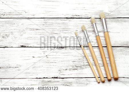 Paint Brushes On White Grunge Wooden Table