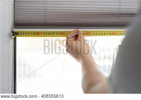 Man Installing Gray Pleated Blinds On The Window