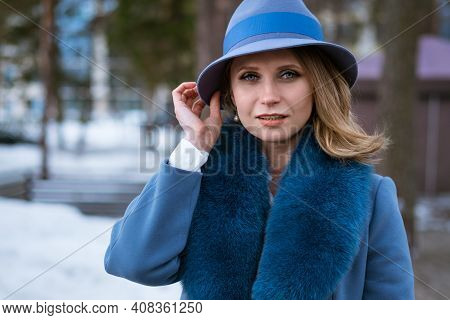 Beautiful Woman With Makeup, In A Blue Coat And Hat, Posing In Nature On The Snow