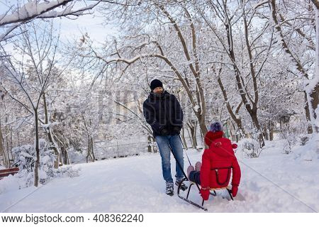 Dad Is Taking His Daughter, A Schoolgirl In A Red Jacket, Through The Winter Park On A Sleigh. Rest