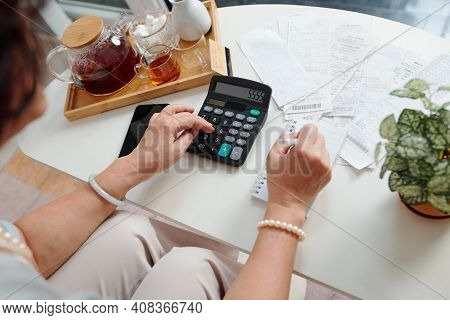 Hands Of Senior Woman Using Calculator To Check Bills And Sum Up Monthly Expenses