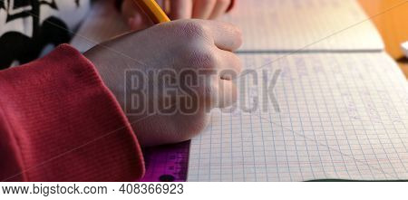 A Child's Hand With A Pencil Writing Solutions To Problems And Examples In A Notebook At A Home Desk