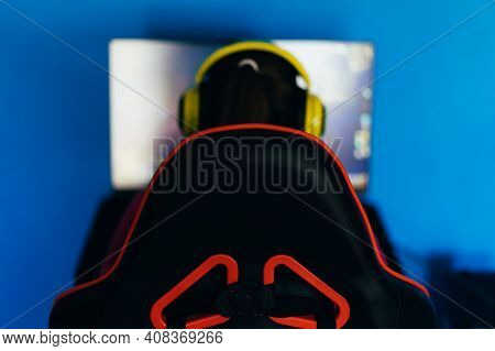 The Gamer Sits On A Gaming Chair And Plays Computer Games. The Player Has Yellow Headphones On His H