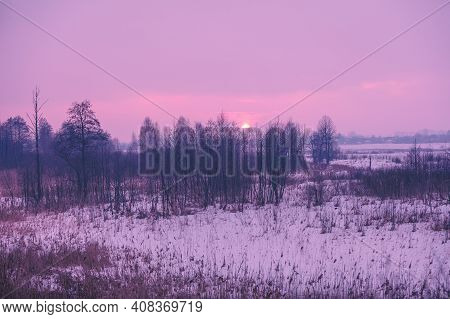 Winter Rural Landscape At Sunset. Winter Snowy Scenery. The Field Covered With Snow At Sunset