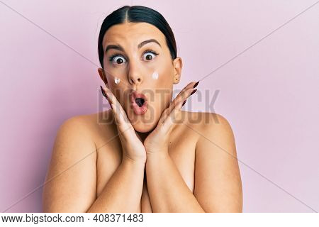 Beautiful brunette woman standing topless wearing face cream afraid and shocked with surprise and amazed expression, fear and excited face.