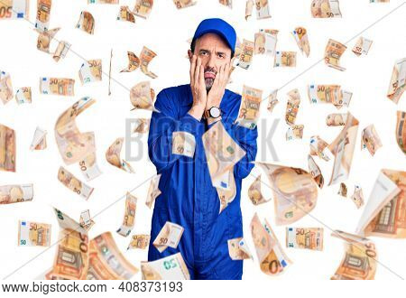 Middle age handsome man wearing mechanic uniform tired hands covering face, depression and sadness, upset and irritated for problem