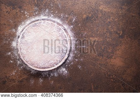 Flour food and pizza cutting board as bakery concept for homemade bread baking on table. Recipe top view at stone background texture with copy space, flat lay concept