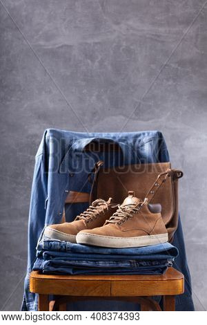 Denim jeans and old boots shoes with leather bag at old wooden chair near grey wall background texture. Modern style of classic jeans fashion